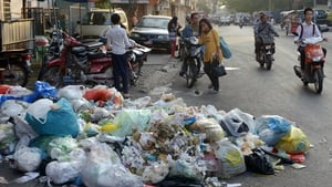 A Cambodian woman walks near a rubbish pile along a street in Phnom Penh. The city's waste management, collection, transport and disposal efforts are in poor condition, leading to environmental and health risks