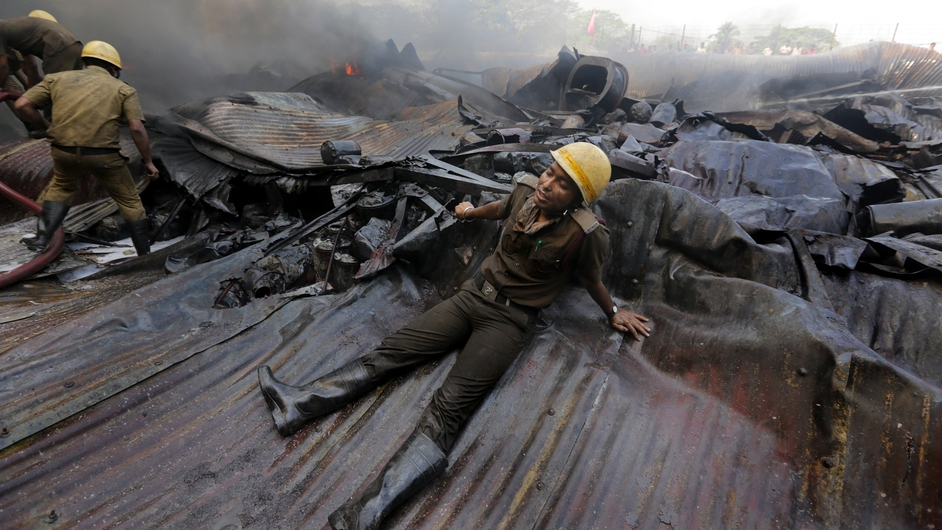 An exhausted firefighter rests on debris as fire crews battle to extinguish a huge fire in a paint factory in Howrah, 30km west of Kolkata, Eastern India. 25 fire engines fought for close to six hours to extinguish the blaze. Nobody was injured (Pic: EPA)