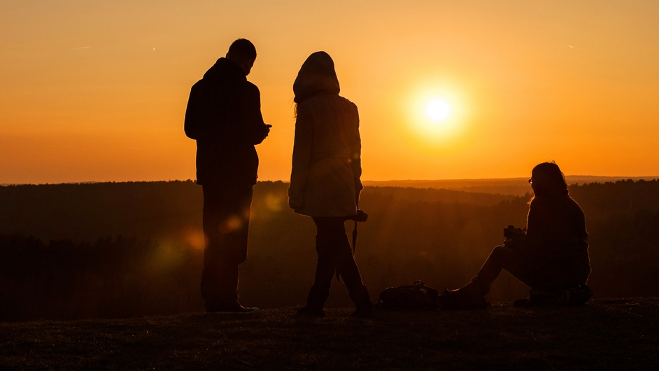 A man and two women watch the sunset from Teufelsberg (Devil's Mountain) in Berlin, Germany (Pic: EPA)