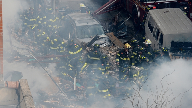A view of firefighters on the scene where a group of buildings were damaged (EPA)
