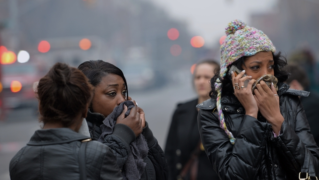 Bystanders cover their faces against smoke as they watch the scene