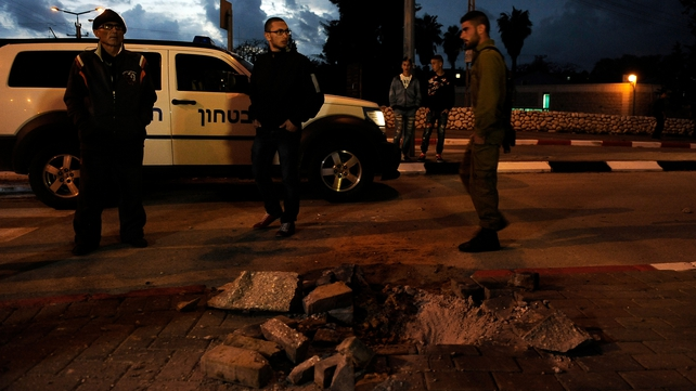 Israeli soldiers and civilians stand next to a hole caused by one of rockets in Sderot
