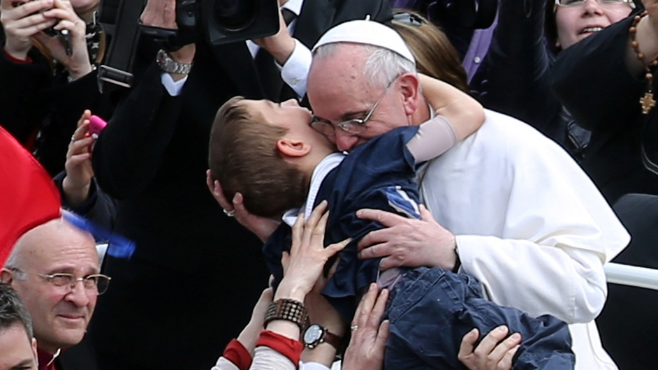 Pope Francis embraces a boy prior to his first 'Urbi et Orbi' blessing from the balcony of St Peter's