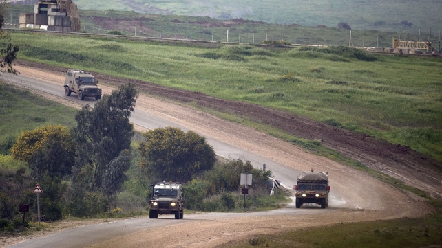 Israeli army vehicles patrol at the border between Israel and Gaza