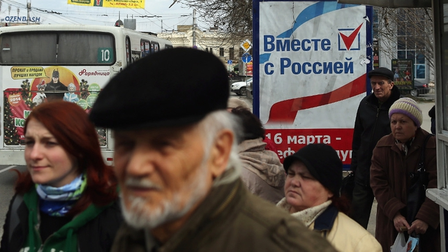 People stand by a sign that reads 'Together with Russia' in Russian at a bus stop in Simferopol, Crimea