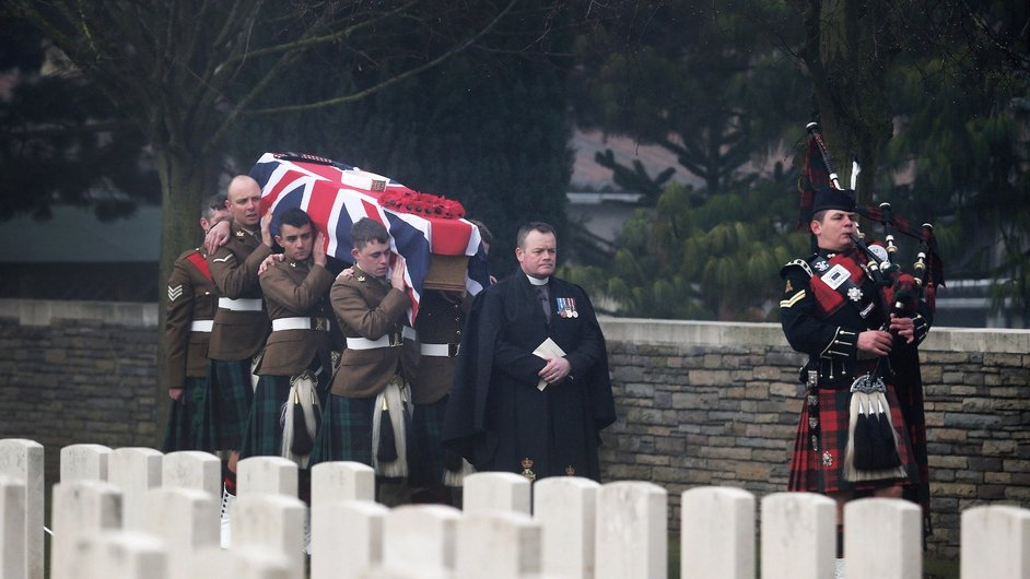 A piper led six bearers as they carried Private William McAleer's Union flag-draped coffin