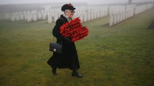 A mourner carries wreaths for the ceremony, which took place at the Loos British Cemetery in Loos-en-Gohelle