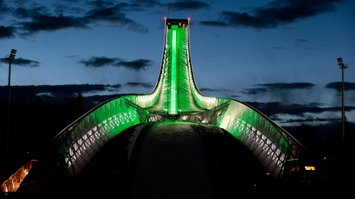 The landmark Holmenkollen ski jump is illuminated in green in Oslo, Norway (Pic: EPA)