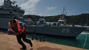 Members of the crew of the Malaysian Navy ship KD Kasturi prepare the ship during refueling and restocking at Kuantan Naval Base in Kuantan, Malaysia