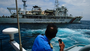 A member of the Malaysian Navy makes a call as their ship approaches a ship belonging to the Chinese Coast Guard during an exchange of communication in the South China Sea