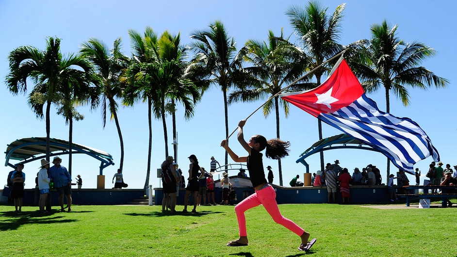 hoshana Finlan runs with the West Papuan flag in a demonstration against the Tony Abbott led coalition government in Townsville, Australia