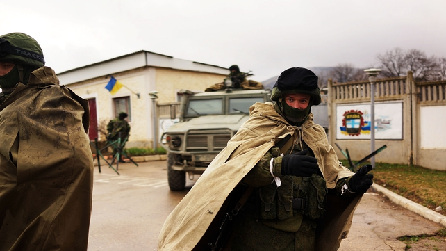Armed soldiers without identifying insignia keep guard outside a Ukrainian military base in the town of Perevevalne