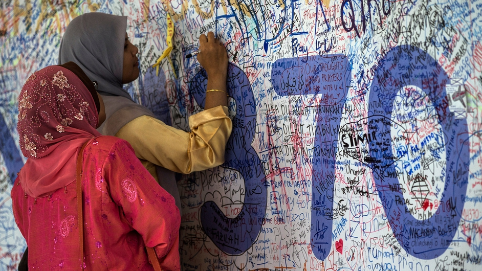 Malaysian women write a message on the Wall of Hope for the missing Malaysian Airlines plane at Kuala Lumpur International Airport (Pic: EPA)