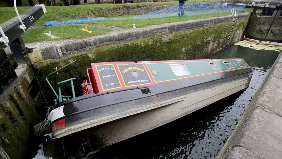 A capsized narrowboat blocks a canal near Bath, England. The canal is currently being drained in order to remove the boat