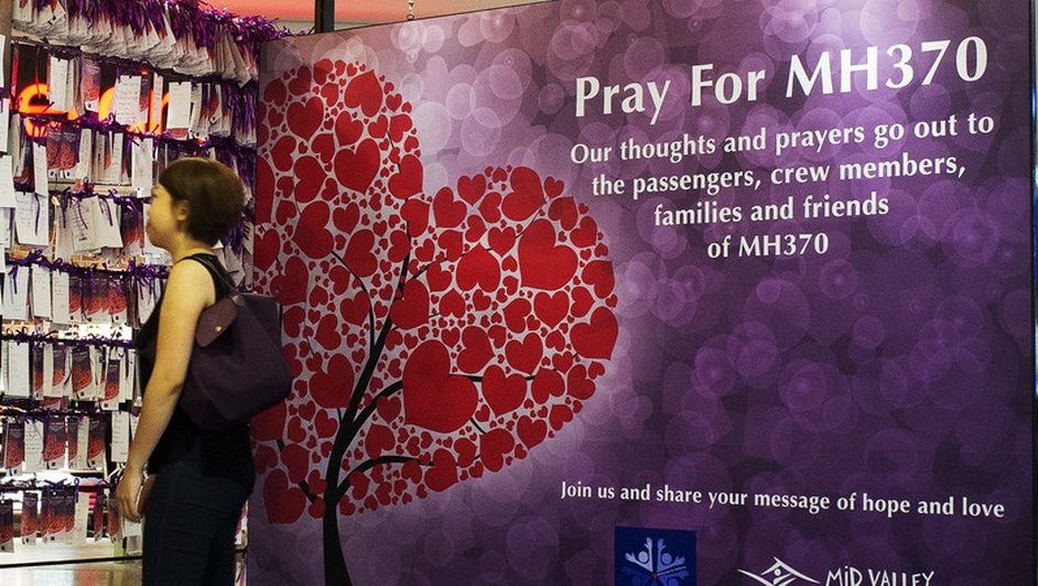 A visitor hangs a message of hope for passengers and crew of the missing Malaysian Airline plane, at a shopping mall in Kuala Lumpur, Malaysia (Pic:EPA)