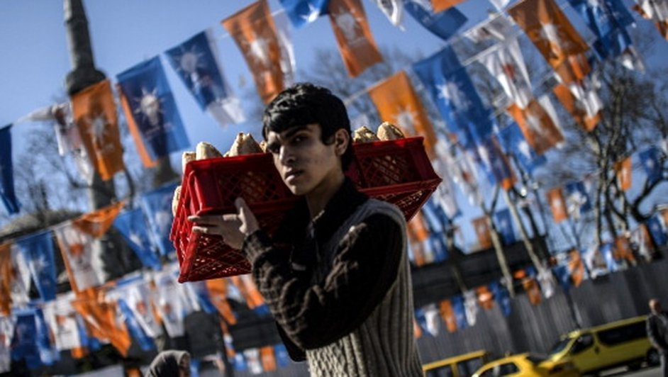 A Turkish boy carries bread by electoral flags in Istanbul, ten days ahead of Turkish local elections.