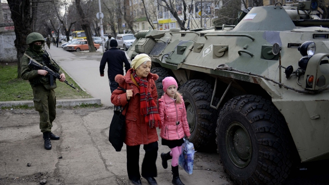 A woman and child pass by Russian military vehicles in Simferopol (Pic: EPA)