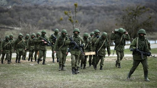 Russian military personnel move towards a Ukrainian military base in Perevalnoe