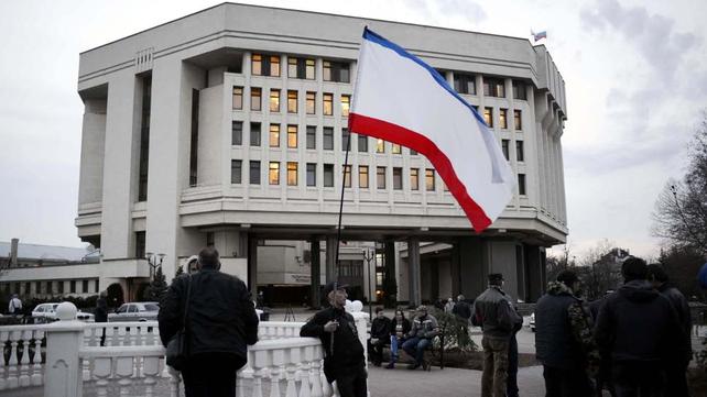 A man holds a Crimean flag outside the Crimean parliament in Simferopol (Pic: EPA)