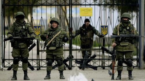 Armed men in military uniform outside a Ukrainian military unit in the village of Perevalnoye, outside Simferopol