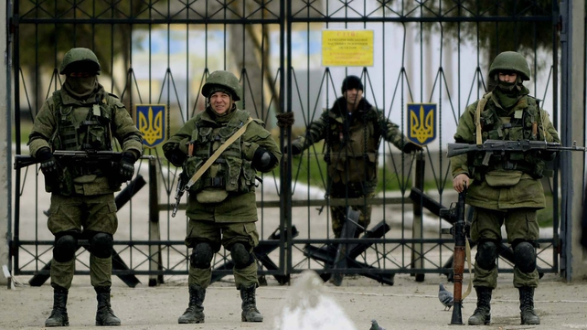 Armed men in military uniform outside a Ukrainian military unit in the village of Perevalnoye, outside Simferopol