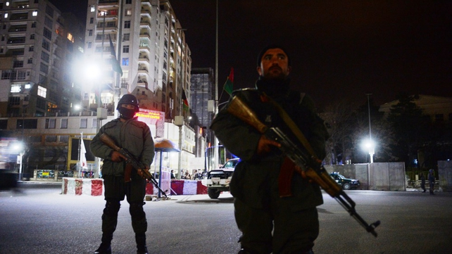 Afghan policemen block a road as they stand guard around the hotel
