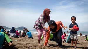 Indonesian residents participate during a tsunami drill on Padang beach in Padang, West Sumatra