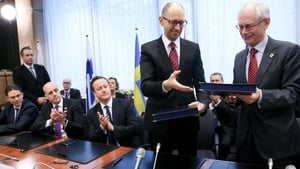 Ukrainian Prime Minister Arseniy Yatsenyuk and EU Council President Herman Van Rompuy exchange documents during the signing ceremony of political provisions of the Association Agreement with Ukraine