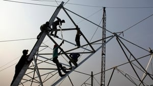 Labourers work without safety equipment to erect electricity pylons in Dhaka, Bangladesh (Pic: EPA)