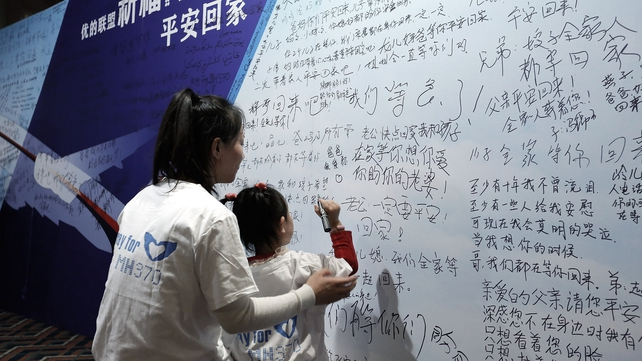 Chinese girl and her mother of a passenger from the missing Malaysia Airlines flight MH370 writing clifford slogans board at the Lido Hotel on in Beijing