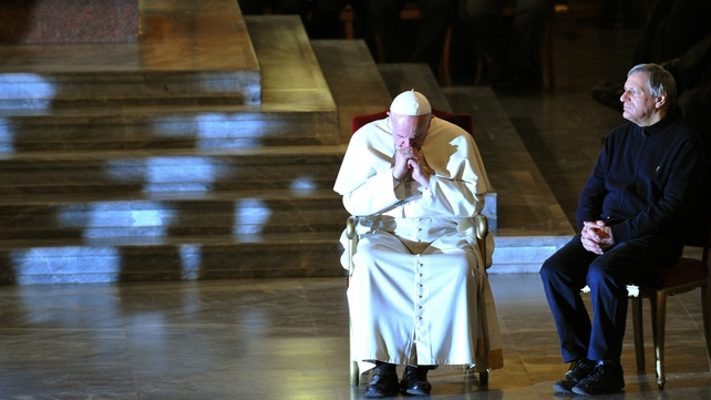 Pope Francis sits next to Father Luigi Ciotti of the Catholic Libera association in San Gregorio church