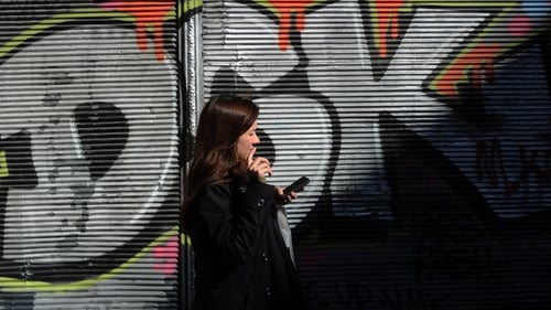 A Turkish woman uses her smartphone as she stands by a graffiti wall, on Istiklal street, in Istanbul