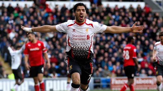 Luis Suarez celebrates after scoring his second and Liverpool's team's fourth