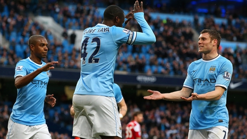 Yaya Toure (c) celebrates scoring City's opening goal from the penalty spot with James Milner