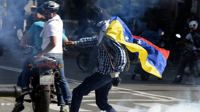 An opponent of Venezuelan President Nicolas Maduro returns a tear gas cannister during a protest in Caracas