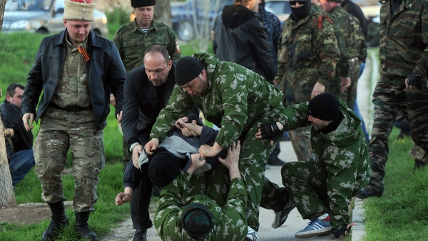 Pro-Russian militiamen beat an unidentified man as Russian soldiers stormed a Ukrainian military air base in the small city of Belbek near the Crimean city of Sevastopol