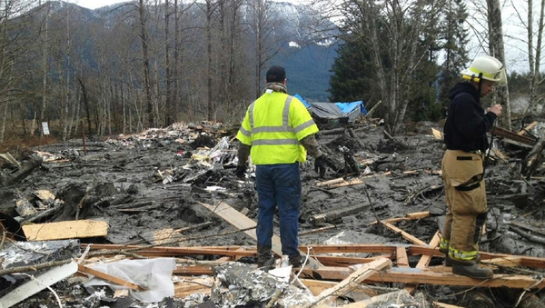 Emergency workers examine debris after a mudslide in Snohomish County, Washington
