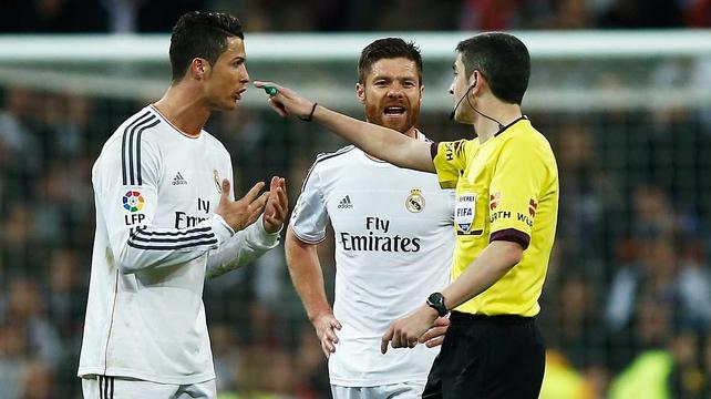 Cristiano Ronaldo (L) and Xabi Alonso of Real Madrid argue with referee Alberto Undiano Mallenco