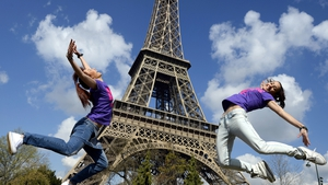 Two Bulgarian tourists pose in front of the Eiffel Tower in Paris on their last day in the French capital