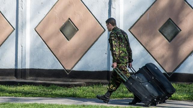 A Ukrainian marine carries his belongings as he leaves his unit in the Crimean port city of Feodosiya
