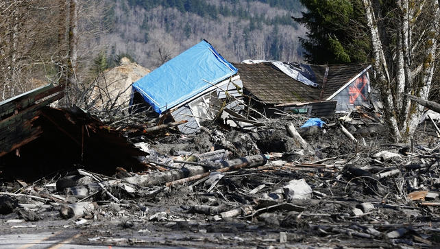 A house sits destroyed in the mud on Highway 530 next to mile marker 37