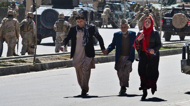 Afghan civilians flee after an Afghan election commission office is attacked by militants