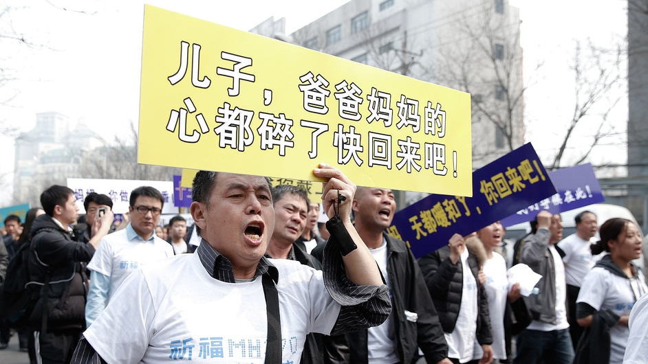 Relatives of the passengers of Malaysian Airlines flight MH370 march to the Malaysian Embassy in Beijing