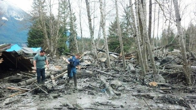 People examine the debris following Saturday's mudslide
