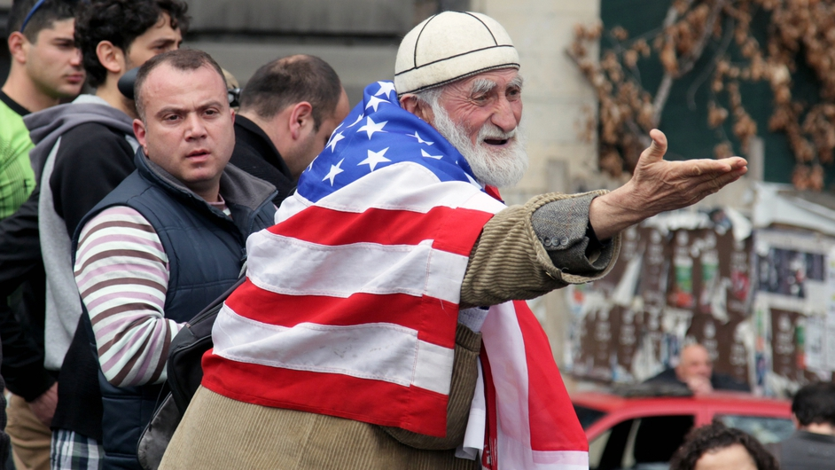 An anti-Russian activist draped in the US flag at a protest in Tbilisi, Georgia (Pic: EPA)