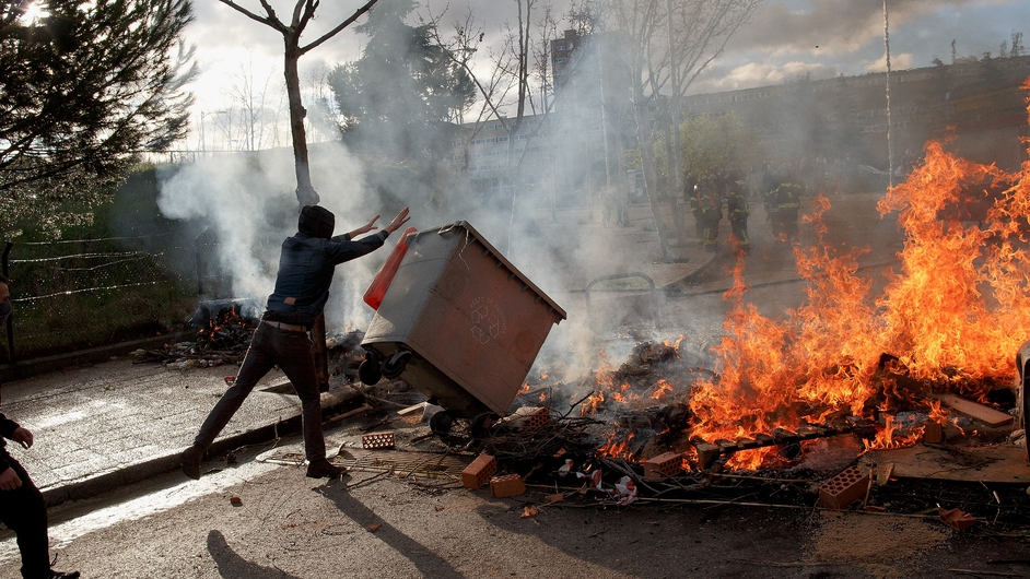 A protester throws a rubbish bin on a burning barricade during protests against education reform in Spain