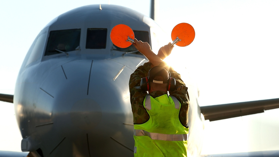 A signalman direct a plane involved in the search for MH370 at a RAAF base in Perth, Australia