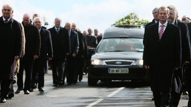 Members of the Fine Gael parliamentary party led by Taoiseach Enda Kenny form the cortege as the hearse leaves Our Lady Queen of Peace Church