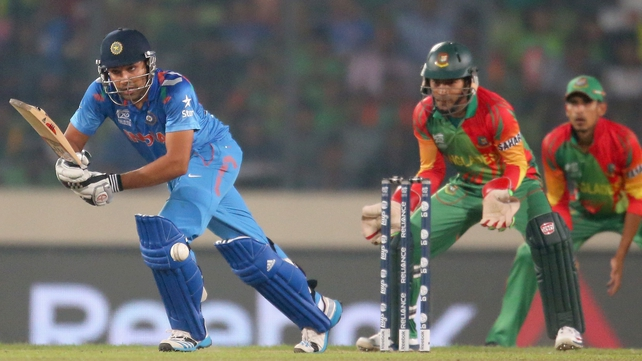 Rohit Sharma bats as Bangladesh wicketkeeper Mushfiqur Rahim looks on