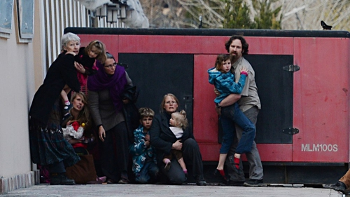 Adults and children take refuge behind a generator after they were evacuated from a guesthouse